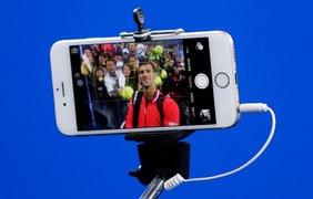 Профессиональный игрок в теннис Новак Джокович делает селфи с болельщиками после победы в Открытом чемпионате Китая в Пекине, 9 октября