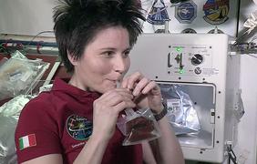 Саманта Кристоферетти на фоне 20-килограмовой кофемашины на борту МКС