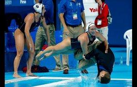 Игроки женской команды США по водному поло толкают в бассейн своего тренера Адама Крикориана после победы над командой Нидерландов на Чемпионате мира по водным видам спорта 2015 в Казани, 7 августа.