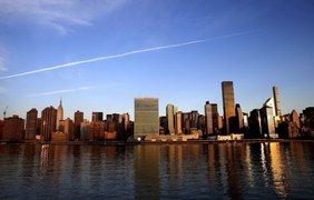 Солнце восходит над штаб-квартирой ООН на Манхэттене в Нью-Йорке