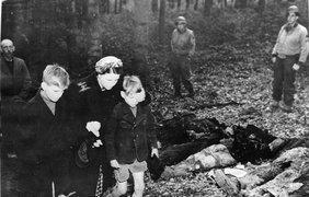 Женщина закрывает рукой глаза своему сыну, чтобы он не видел погибших тел