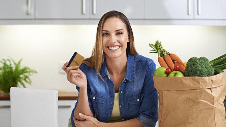 Девушка с банковской картой и пакетом продуктов