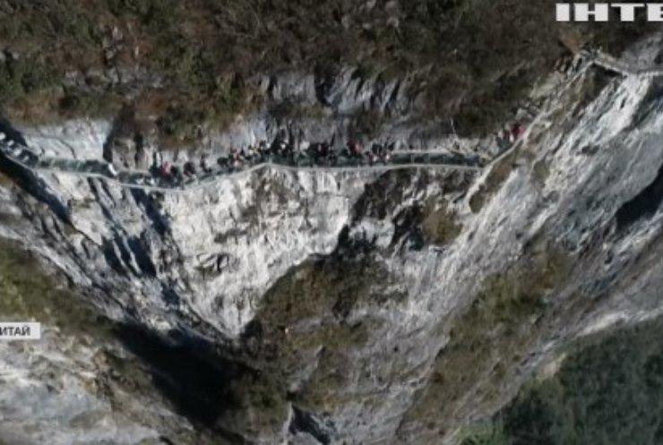 У Китаї команда альпіністів збирає сміття на скелях